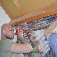 man maakt dampwerende folie vast aan dakconstructie